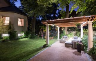 A garden with covered patio at night